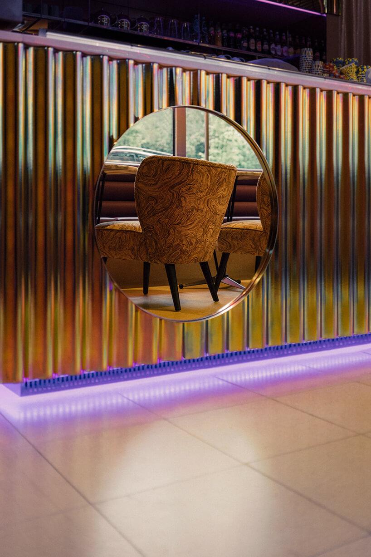 wykończenie lady zbłyszczących rurek izłotych luster we wnętrzu kilka stolików zzielonymi fotelami we wnętrzu Lukullus lodziarnia Warszawa