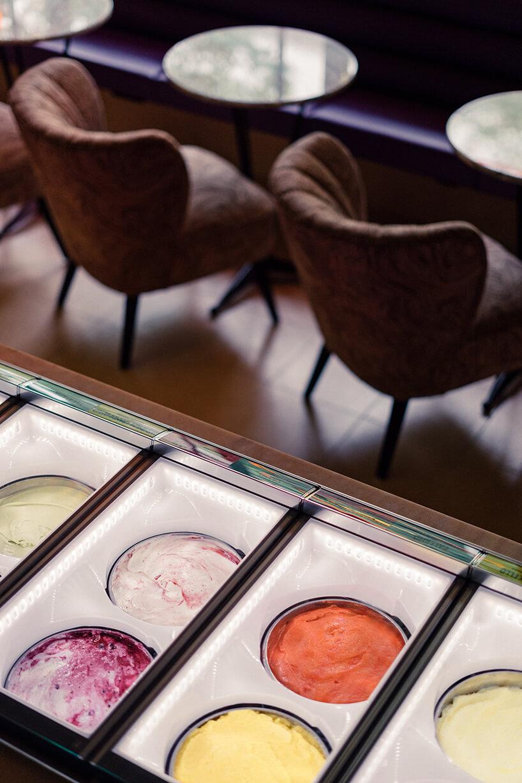 zdjęcie pojemników zlodami na tle brązowych krzeseł przy stolikach we wnętrzu kilka stolików zzielonymi fotelami we wnętrzu Lukullus lodziarnia Warszawa
