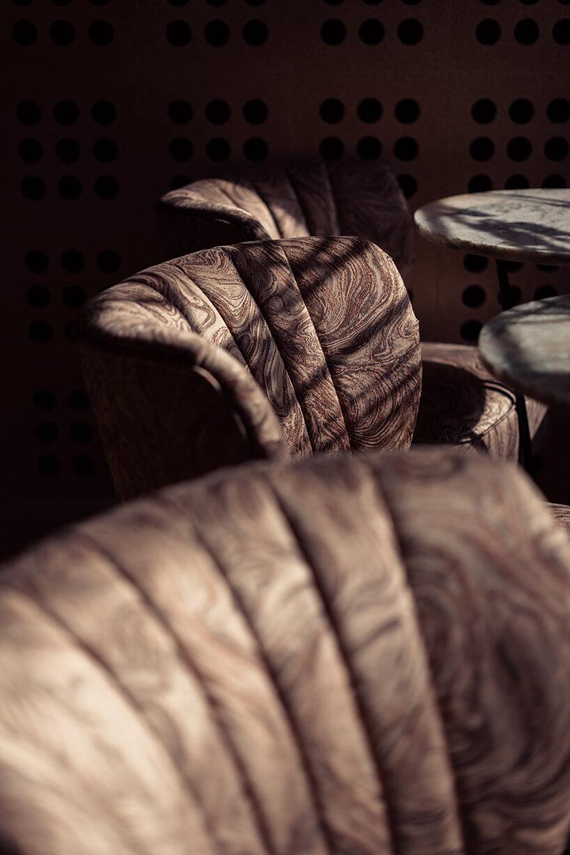 wzorzyste brązowe oparcia foteli wkilka stolików zzielonymi fotelami we wnętrzu Lukullus lodziarnia Warszawa