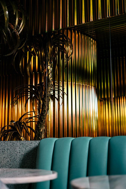 błyszczące wykończenie ścian jako tło dla wysokiej rośliny wkilka stolików zzielonymi fotelami we wnętrzu Lukullus lodziarnia Warszawa