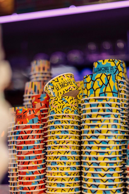 kolorowe iwzorzyste papierowe kubki do lodów kilka stolików zzielonymi fotelami we wnętrzu Lukullus lodziarnia Warszawa