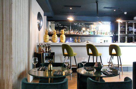 wnętrze baru wysokimi zielonymi siedziskami z oparcie i złotymi ananasami na barze