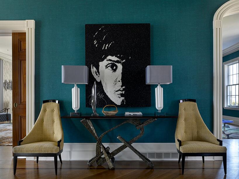 czarno-biały obran na zielonej ścianie pomiezy dwoma lampami na czarnym stole znietypową podstawą