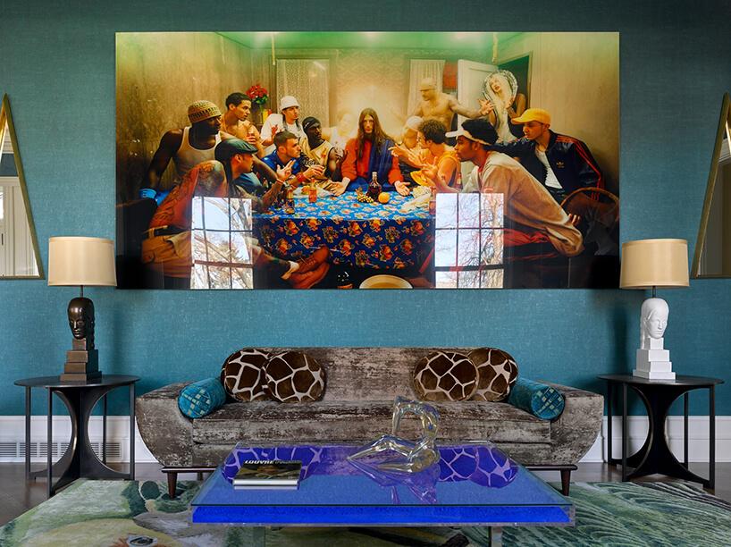 wielki obraz na niebieskiej ścianie na brązową sofą