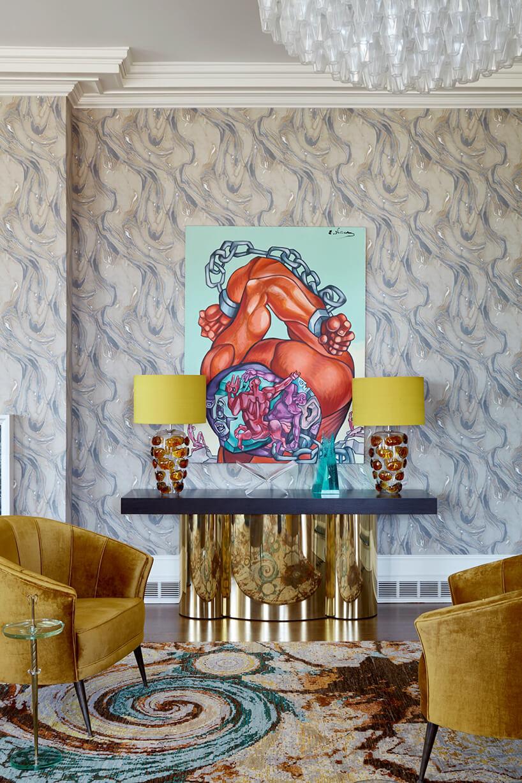 dwa złote fotele istolik pod ścianą zniebieskim blatem izłotą podstawą