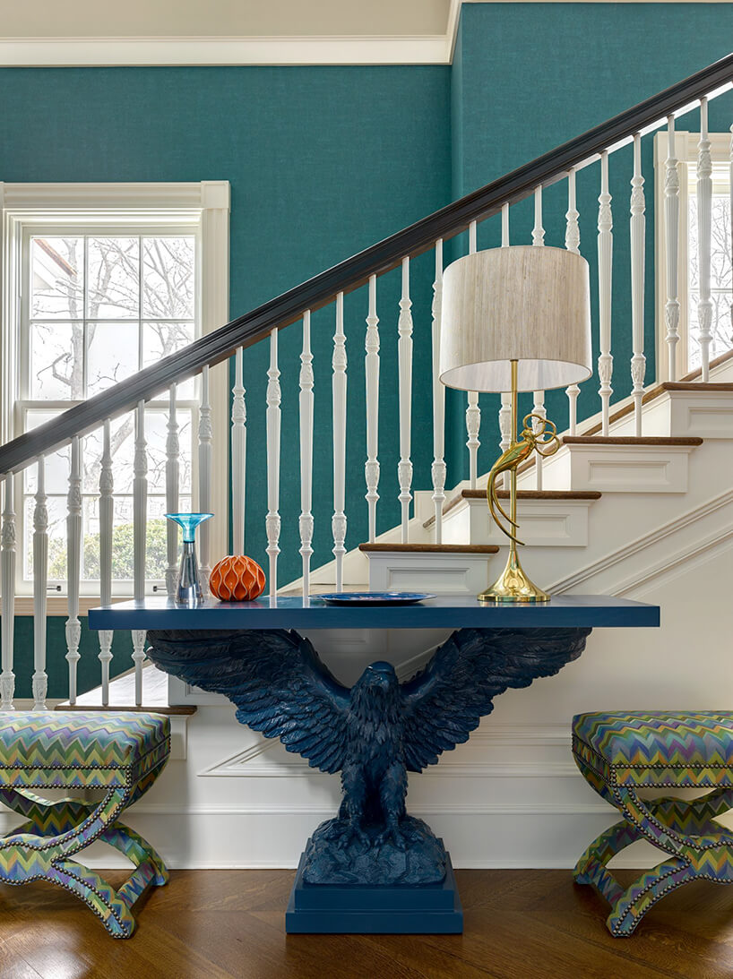 niebieski stół zpodstawą wkształcie orła zrozłożonymi skrzydłami na tle biało-brązowych schodów