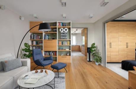 jasno dębowa podłoga w szarym doświetlonym pomieszczeniu z niebieskim wygodnym fotelem i czarną lampą wiszącą