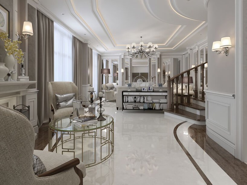 eleganckie białe wnętrze zbiała kamienną podłogą zbrązowym pasem pod ścianami wyjątkowym okrągłym stolikiem ze złotych metalowych prostokątów