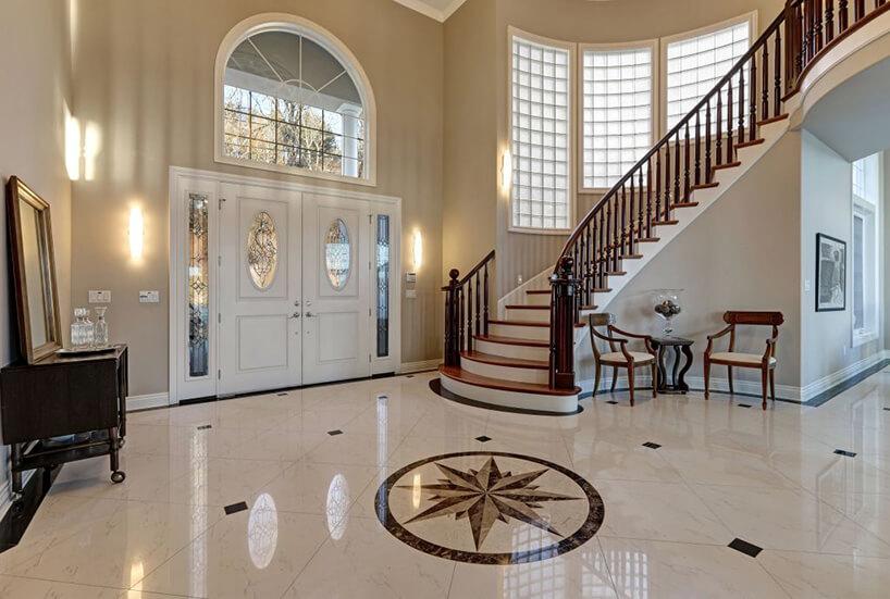 elegancka posadzka zbiałego marmuru zbrązową różą wiatrów po środku holu przy dwuskrzydłoych białych drzwiach wejściowych ze zdobionymi szybkami przy drewnianych schodach