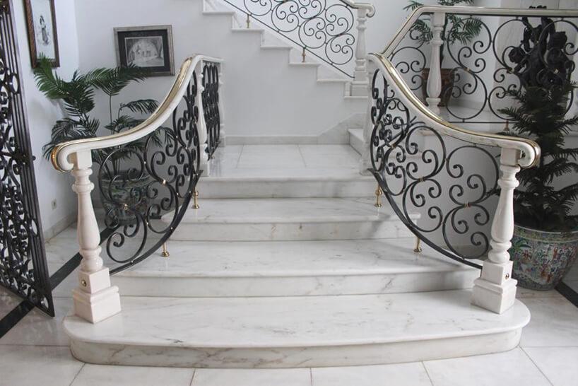 białe marmurowe schody zczarną balustradą zmetalowych elementów pod białą poręcza ze złotem wykończeniem