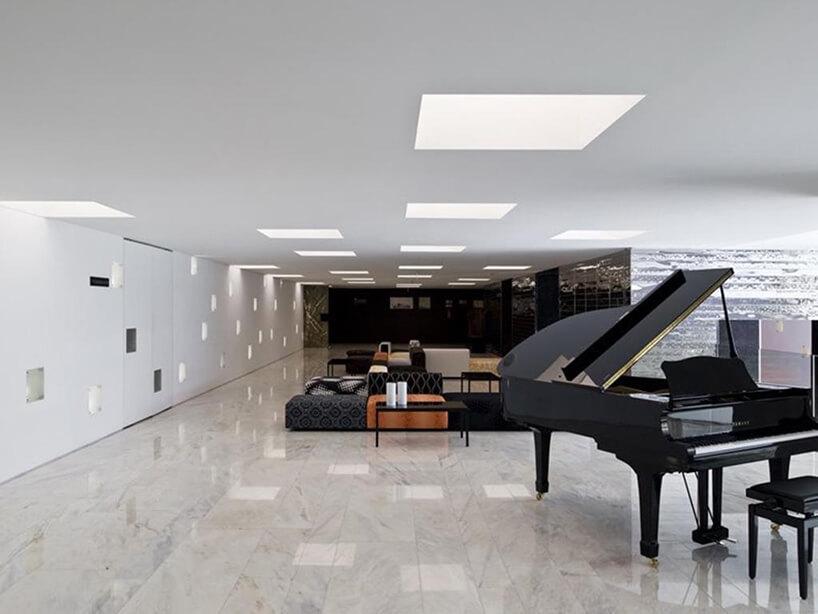 duża przestrzeń zbiałą marmurową posadzką ztrzema czarnymi błyszczącymi ścianami jako tło dla fortepianu ikilku siedzisk