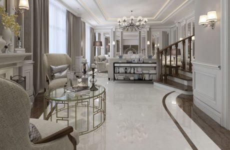 eleganckie białe wnętrze z biała kamienną podłogą z brązowym pasem pod ścianami wyjątkowym okrągłym stolikiem ze złotych metalowych prostokątów