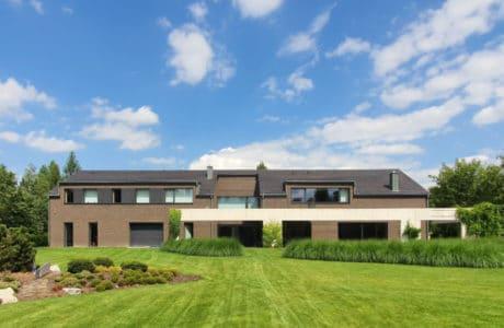 duży dom z brązowo białą elewacją na zielonej działce