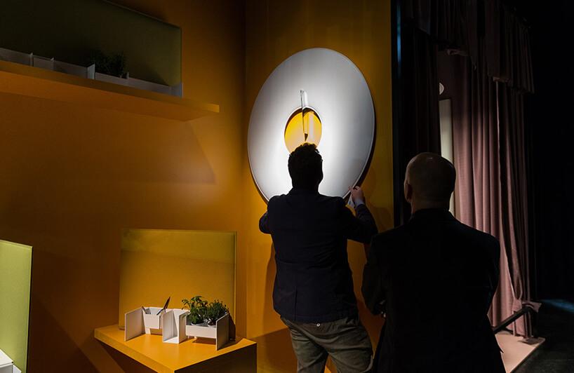 dwóch mężczyzny przy stoisku zpomarańczowymi ścianami idużym zegarze