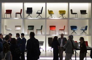 ludzie na tle ściany z poustawianymi ku górze kolorowymi krzesłami