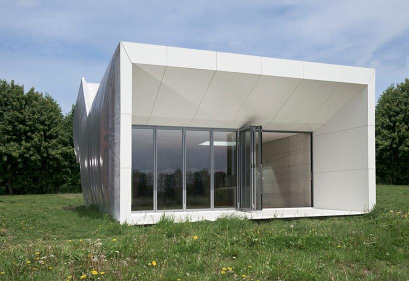 biały Wormhouse Dom robak projektu Piotra Kuczia zdjęcie od przodu na zielonej łące