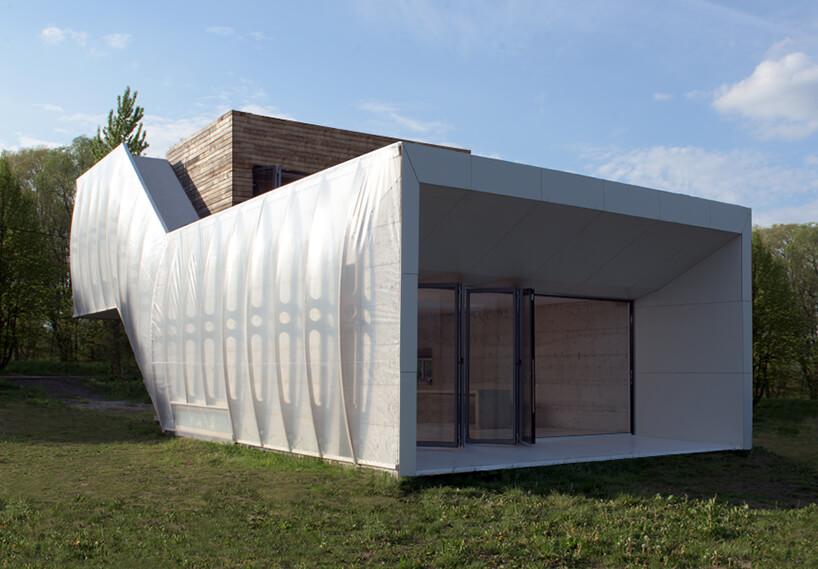 biały Wormhouse Dom robak projektu Piotra Kuczia owinięty folią zboku