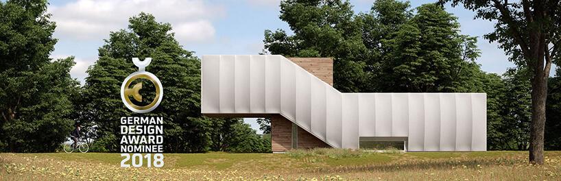 biały Wormhouse Dom robak projektu Piotra Kuczia zdjęci zboku na tle drzew