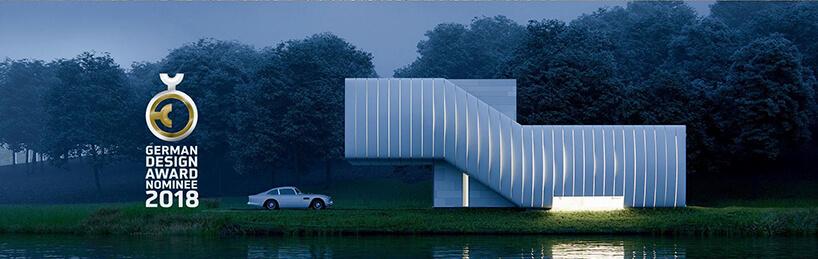 biały Wormhouse Dom robak projektu Piotra Kuczia zdjęcie podświetlonego budynku wieczorem