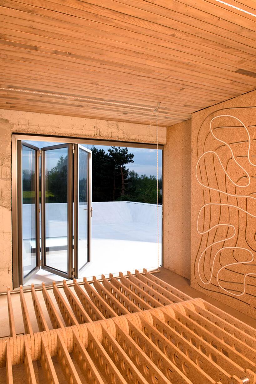 drewniane wnętrze Wormhouse Dom robak projektu Piotra Kuczia zotwartymi drzwiami wieloczęściowymi