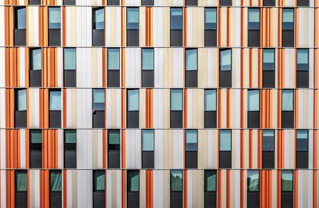 zdjęcie eelewacji nowoczesnego budynku z czarnymi oknami i pomarańczowo biało beżową elewacją