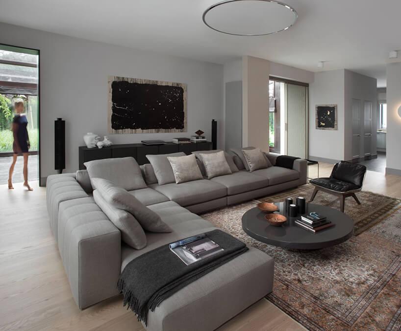 duży elegancki salon zdużą narożną szarą sofą