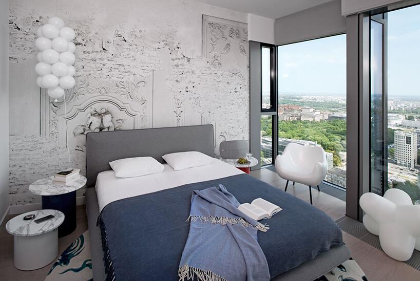 elegancka sypialnia zwidokiem na miasto zwyjątkową tapetą ilampą wkształcie balonów