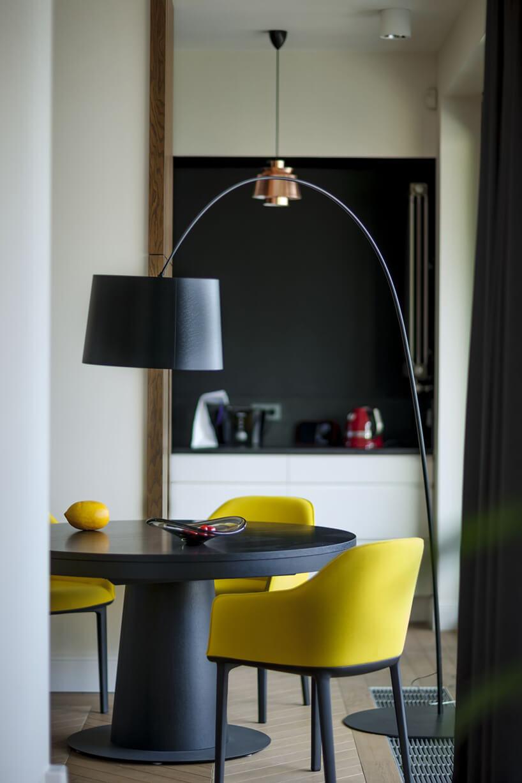 wyjątkowa lampa nad czarnym okrągłym stołem ztrzema żółtymi krzesłami