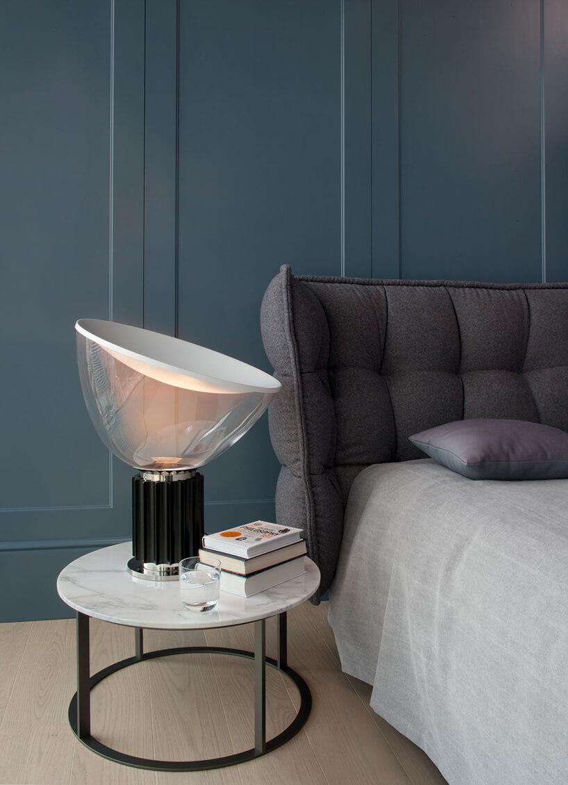 wyjątkowa lampka nocna zczarną podstawa na tle niebieskiej ściany obok szarego łóżka