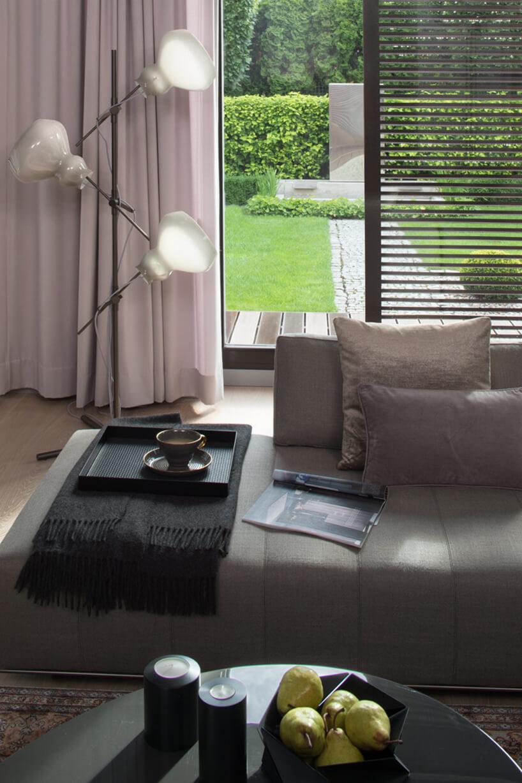 salon zszarą sofą na tle lampy stojącej ztrzem kloszami iprzeszklonych drzwi tarasowych