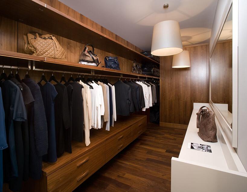 ekskluzywna drewniana długa garderoba wbrązie zdużym lustrem zbudowanym na biało