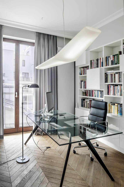 nowoczesny gabinet zbiałą szafką na książki ze szklanym biurkiem ilampa wiszącą wkształcie skrzydła