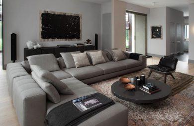 duży elegancki salon z dużą narożną szarą sofą