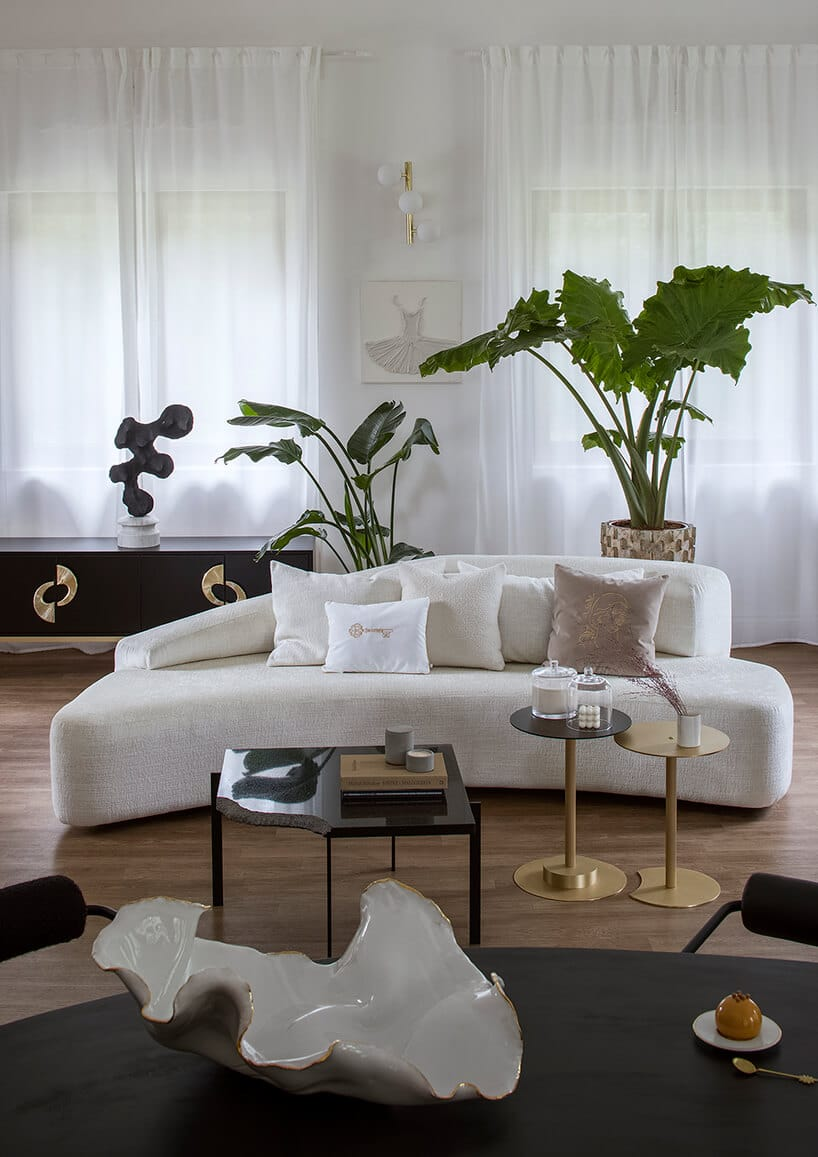 kremowa kanapa wkształcie banana zpoduszkami stojąca na podłodze zdrewna