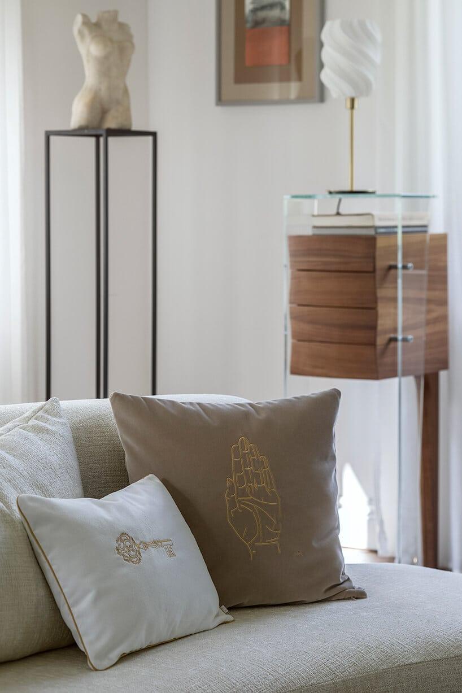 ciemnobeżowa poduszka ze złotym konturem dłonina jasnej kanapie obok szklanego mebla