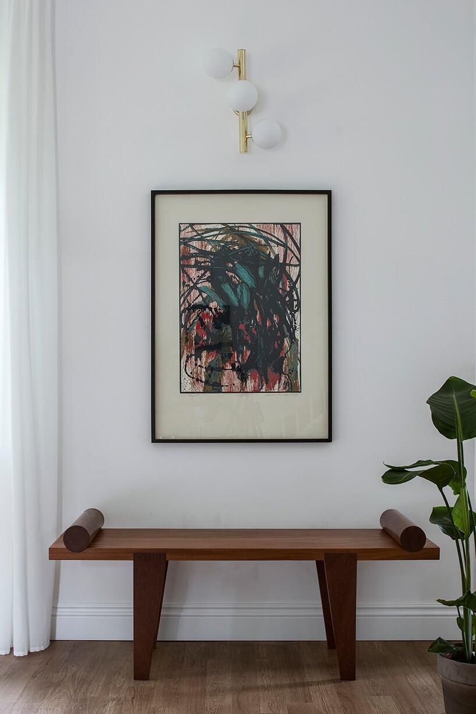 miedziano-brązowa ława zdługim blatem zzaokrągleniami pod wiszącym obrazem na ścianie
