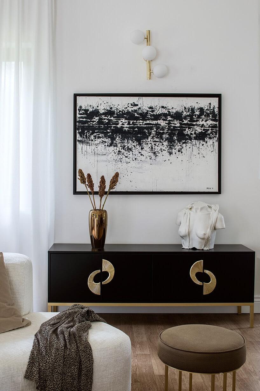 czarna matowa komoda ze złotymi zdobieniami oraz białym porcelanowym popiersiem