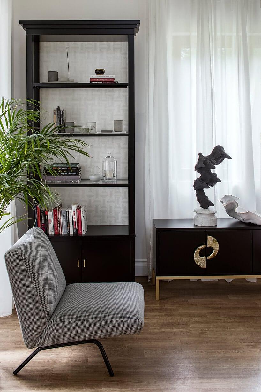 fotel wszaro-czarną kratę obok wysokiego regału wkolorze ciemnego dębu