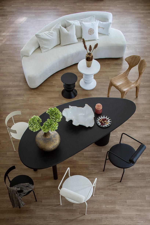 czarny nieregularny stolik wczarnym macie zpięcioma krzesłami wróżnych kolorach