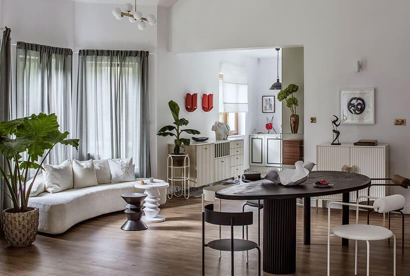 biała kanapa zczterema białymi poduszkami przy zielonej roślince wpomieszczeniu zszarymi zasłonami oraz stołem