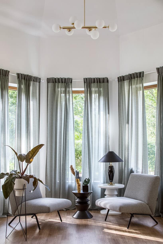 długie ciemno szare zasłony na brązowych aluminiowych oknach wjasnym pomieszczeniu zfotelami