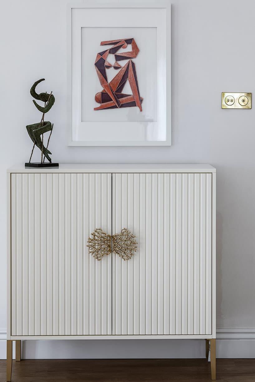biała szafka zfakturą na drewnianych nóżkach zozdobnymi uchwytami