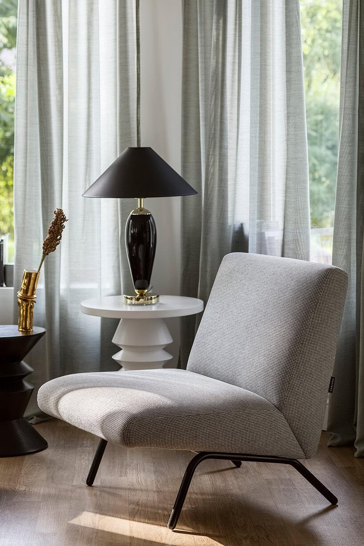fotel zpapitą na czarnej metalowej konstrukcji wsalonie przy stoliku zczarną lampą