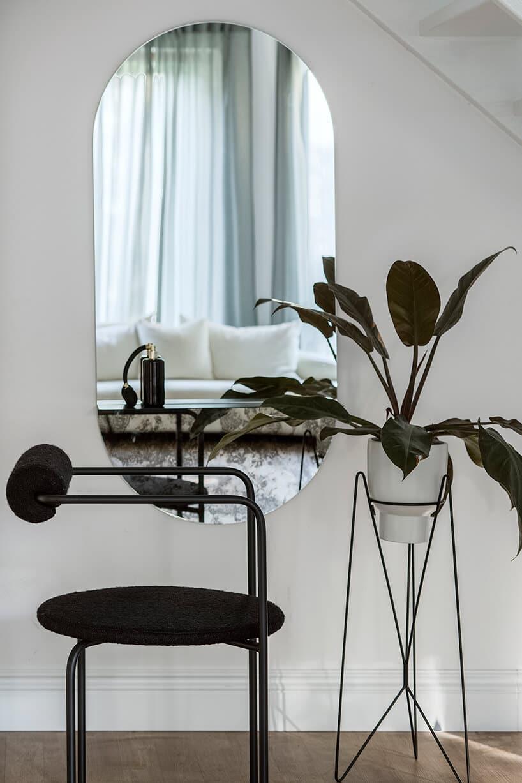 duże owalne lustro przy roślinie wdoniczce na metalowym stojaku