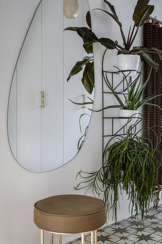 lustro wkształcie gruszki na ścianie wpomieszczeniu zgwieździsta podłogą oraz brązowym stołkiem