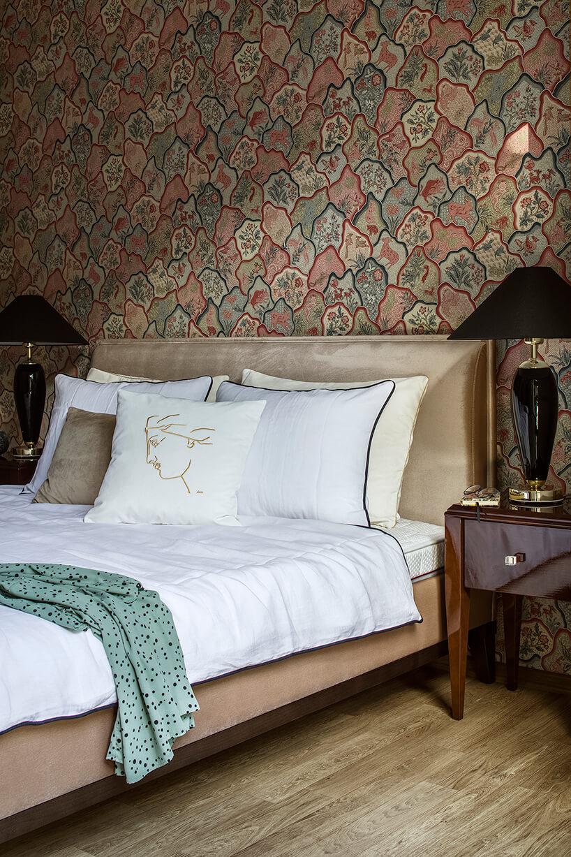 łóżko zbiałymi poduszkami zhaftem stojące pryz ścianie zwzorzystą tapetą