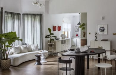 biała kanapa z czterema białymi poduszkami przy zielonej roślince w pomieszczeniu z szarymi zasłonami oraz stołem