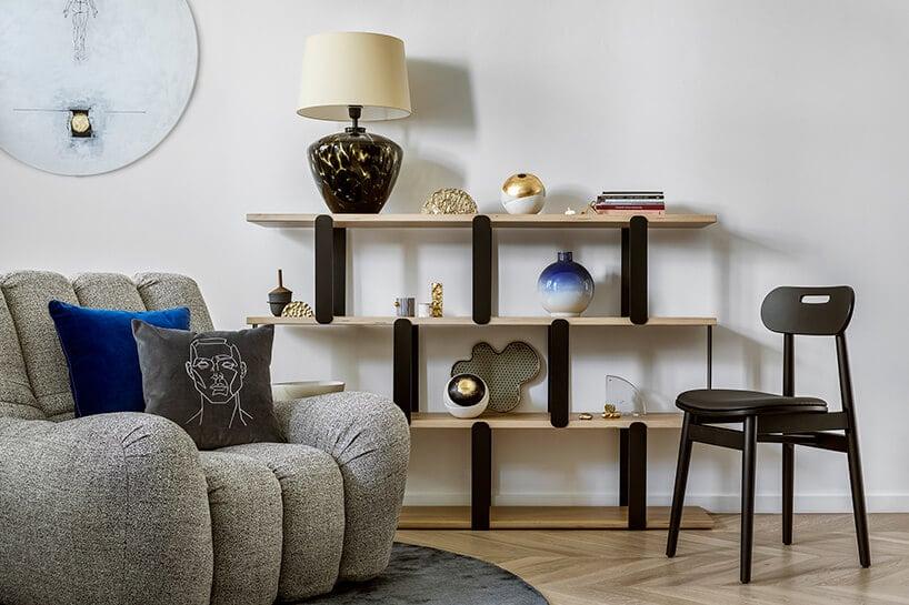 mieszkanie wstylu retro zszarą puszystą kanapą przy regale zdrewnianymi półkami oraz czarnymi podporami
