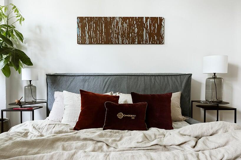 łóżko zbiała pościelą oraz bordową poduszką na środku zszarym zagłowiem