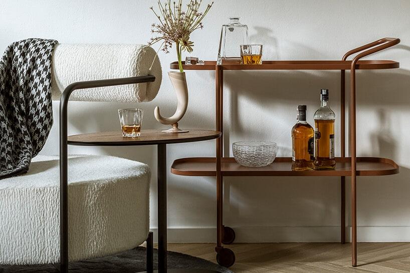 metalowy brązowy stolik na kółkach zpółkami przy białej ścianie na parkiecie